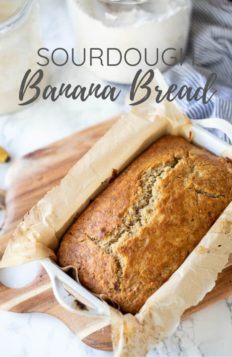 sourdough banana bread in a loaf pan covered in parchment paper. Loaf sits on a wood cutting board