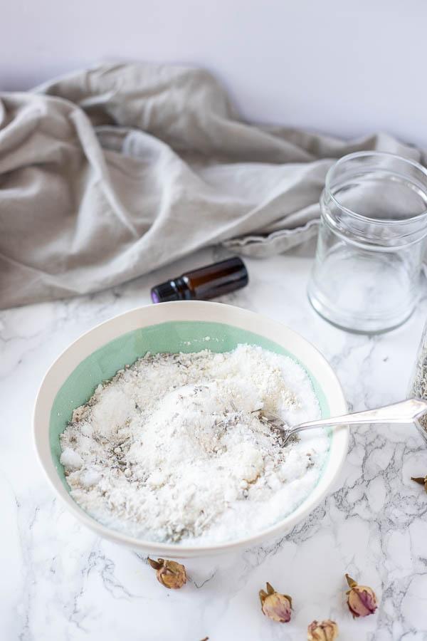 bowl of bath salts, dried herbs, essential oils stirred in a bowl