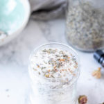 DIY bath salts with dried flowers in a glass jar. A bowl and a jar of dried lavender in the background