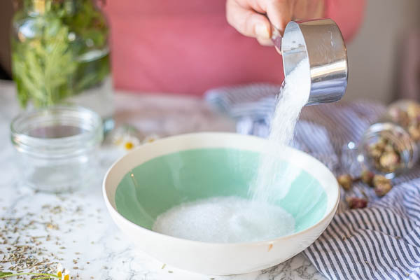 adding Epsom salts to a a teal bowl with baking soda in it