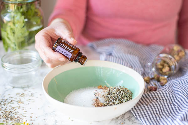 women wearing pink shirt adding essential oils to a bowl of homemade foot soak