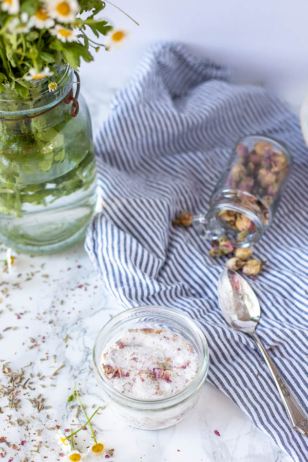small jar of diy foot soak topped with dried flowers. A jar of fresh chamomile and another jar of dried roses on a blue and white napkin are in the background