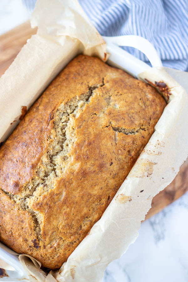 overhead close up photo of sourdough banana bread with a white and blue towel in the background