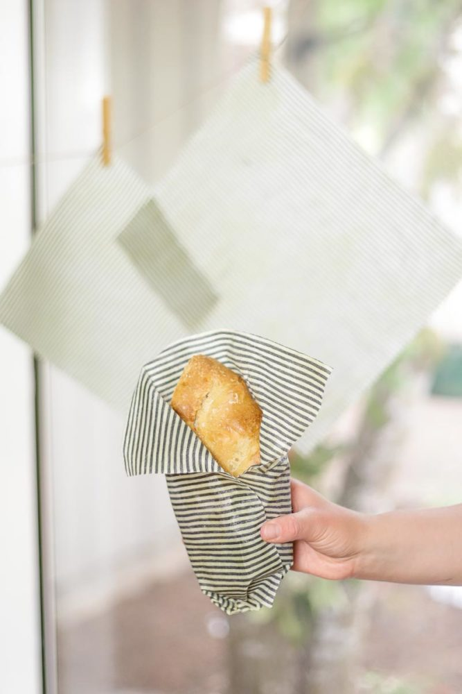 hand holding bread wrapped in beeswax fabric wrap with more wraps hanging on a line in the background