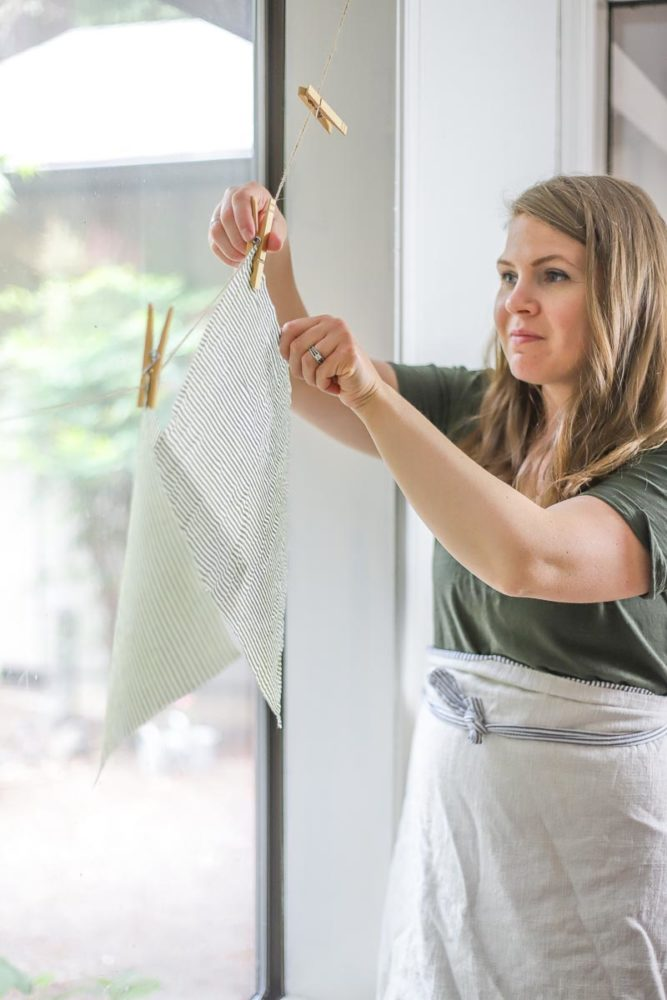 women wearing a green dress and an apron is hanging beeswax wraps on a clothes like with clothes pins