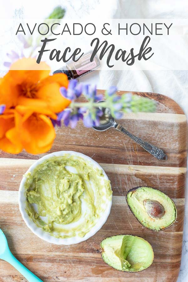Avocado face mask in a white dish on a cutting board with an avocado to the right and wild flowers in the background