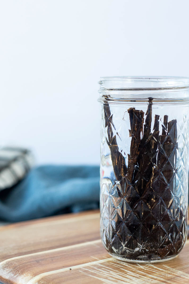 a glass jar of vodka with vanilla beans in it to make homemade vanilla extract