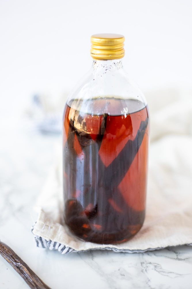 homemade vanilla extract in a glass bottle on a cream colored towel with a vanilla bean to the left