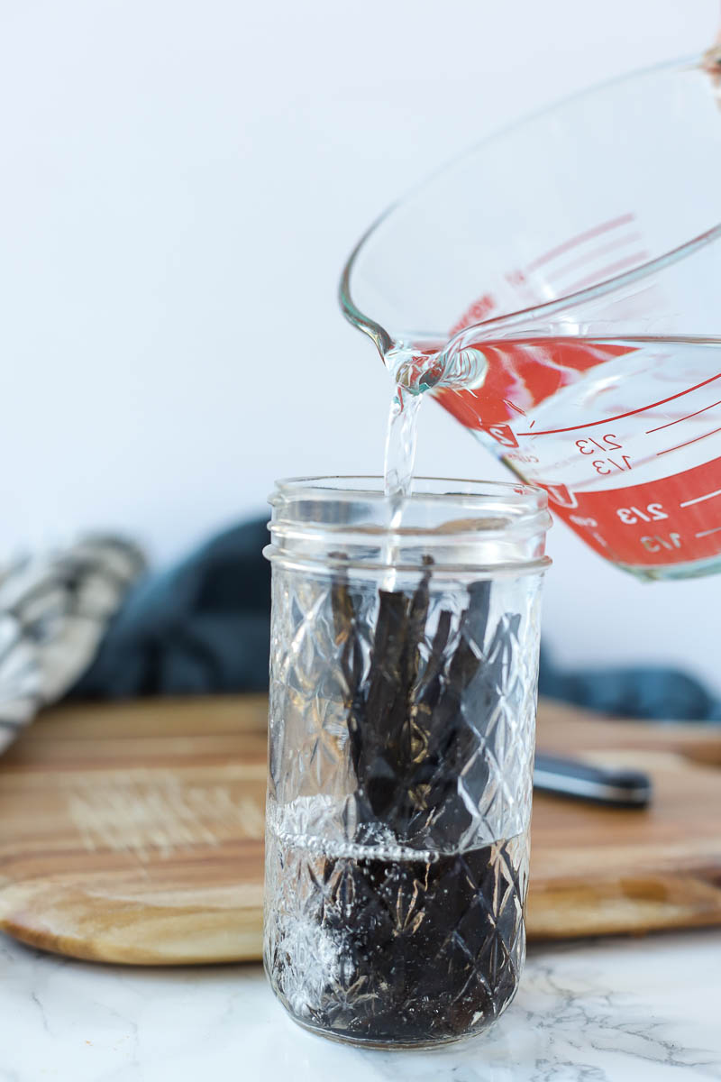 vodka being poured over vanilla beans in a glass jar.