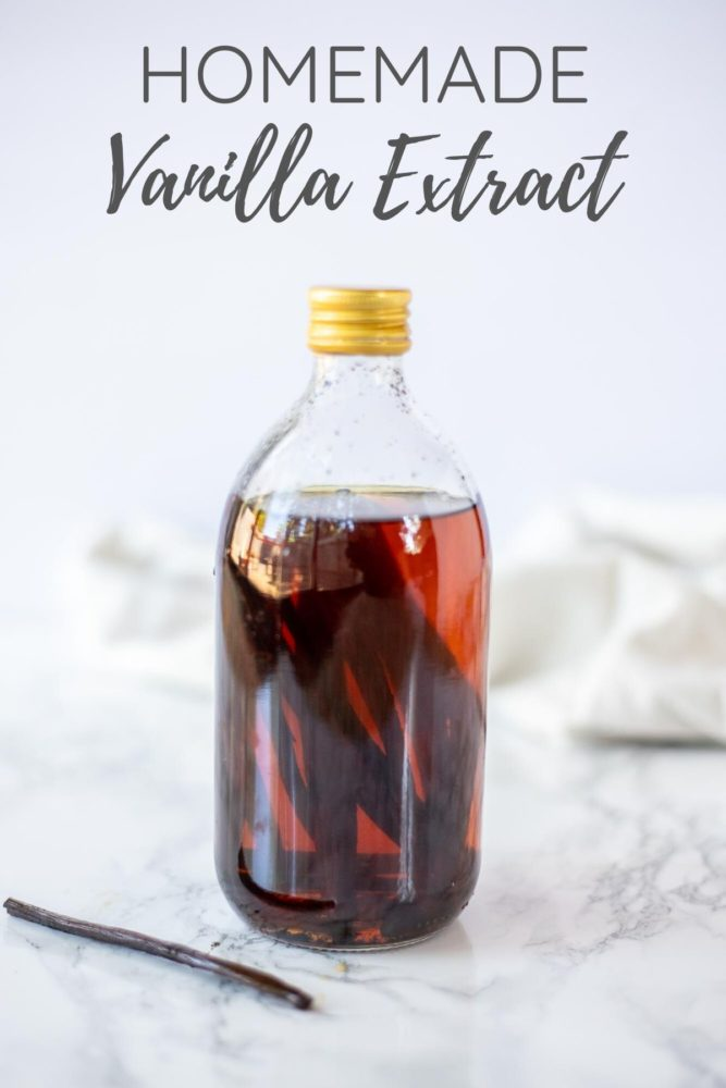 homemade vanilla extract in a bottle with a vanilla bean in front.