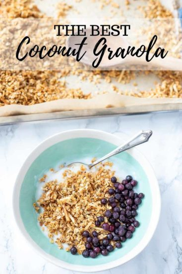 coconut granola in a bowl with yogurt and frozen blueberries. Pan of baked oatmeal in the background