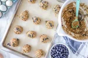 blueberry oatmeal cookie dough on parchment paper lined cookie sheet ready for baking.