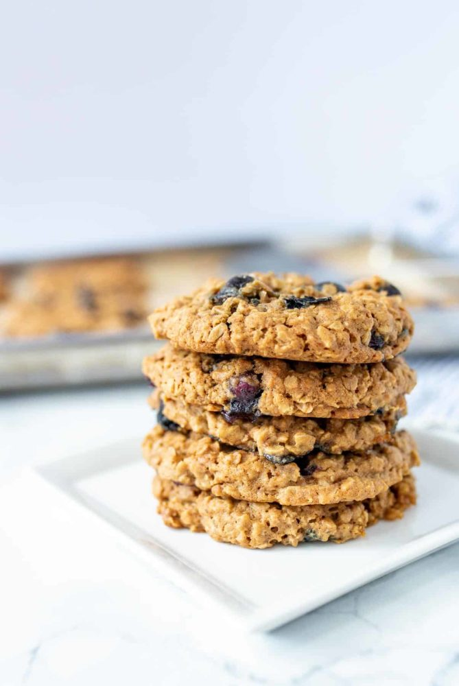 5 blueberry oatmeal cookies stacked up on a square white plate with more cookies on a baking sheet in the background