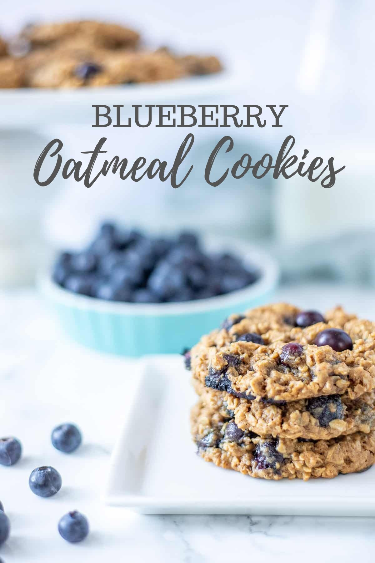 three blueberry oatmeal cookies stacked on a white plate with fresh blueberries to the left and in the background