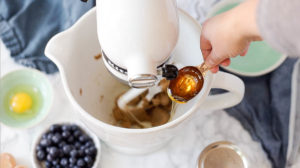 adding honey to a stand mixer of coconut sugar and softened butter to whip until fluffy for blueberry oatmeal cookies