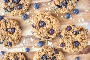 blueberry oatmeal cookies on a wood cutting board with oats and fresh blueberries surrounding the cookies