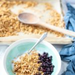 coconut granola with yogurt and blueberries in a teal and cream colored bowl. A pan of freshly baked coconut granola in the background