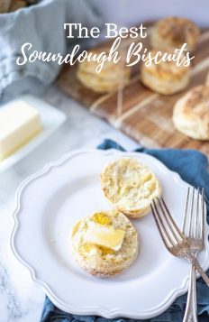 sourdough biscuits split in half with a pat of butter and honey being drizzle on. Biscuit on a white plate with two antique forks on it and a wood cutting board with biscuits in the background