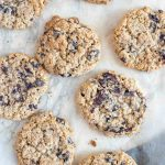 freshly baked oatmeal chocolate chip cookies on parchment paper