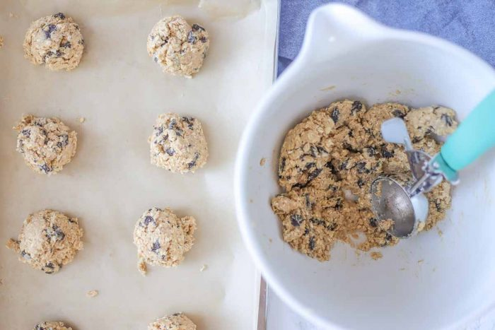 oatmeal chocolate chip cookies being scooped onto a parchment lined baking sheet.