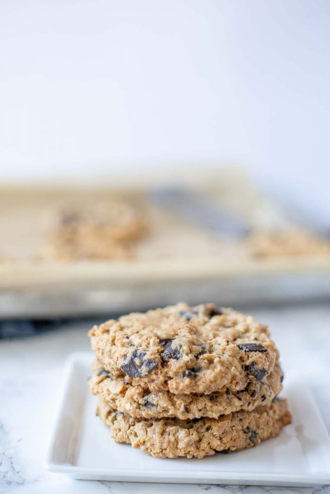 three chocolate chip oatmeal cookies stacked up on a white plate with a pan of cookies in the background