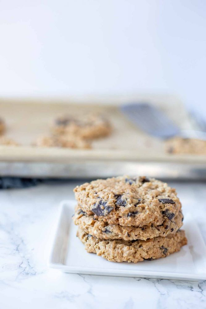 three chocolate chip oatmeal cookies stacked on a white plate