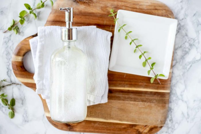 natural soap in a glass jar on a white dish cloth on a wood cutting board with a white plate to the right