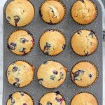muffin pan of sourdough blueberry muffins on a marble countertop with a napkin to the top right
