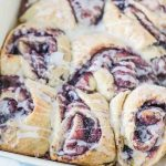 close up of a baking dish of blueberry sourdough sweet rolls with icing