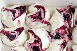 raw blueberry rolls in a baking dish ready for baking