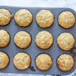 sourdough banana muffins in a muffin tin on a cream and blue stripped towel