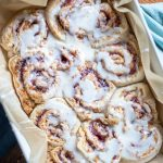 sourdough raspberry rolls covered with icing in a parchment lined baking sheet on a blue towel