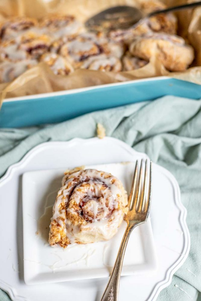 overhead photo of sourdough raspberry rolls on a white plate with a blue baking dish of more rolls in the background