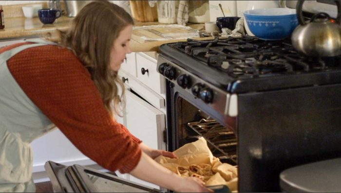 women wearing an orange sweater and an apron placing raspberry rolls in the oven