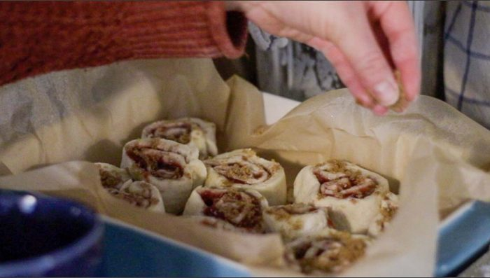hand sprinkling sourdough raspberry rolls with brown sugar before baking