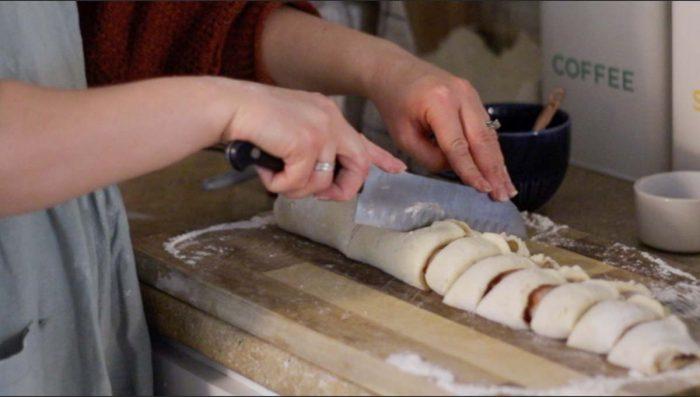 women slicing sourdough raspberry roll dough  on a cutting board