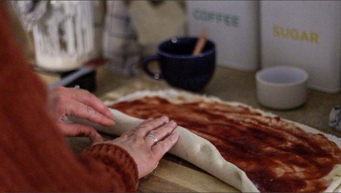 women wearing an orange sweater rolling sourdough biscuit dough smothered in raspberry jam