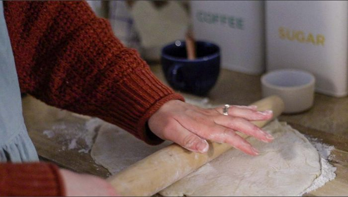women wearing an orange sweater rolling out raspberry roll dough on a floured cutting board
